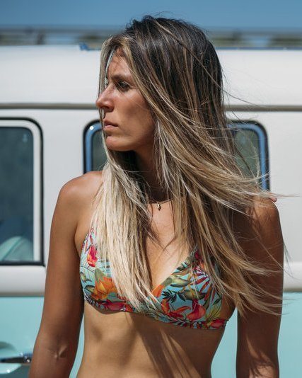 Surfer woman with a van on the beach